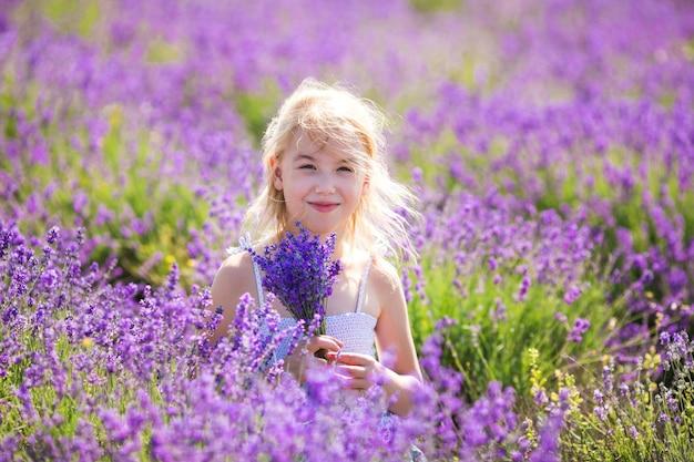 Fille blonde dans la robe de couleur dans le champ de lavande avec un petit bouqet dans ses mains