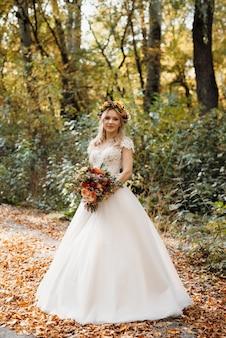 Fille blonde dans une robe de mariée dans la forêt d'automne