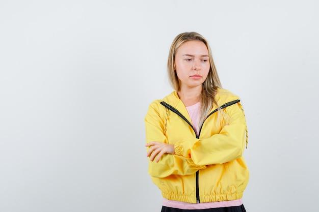 Fille blonde debout les bras croisés en t-shirt rose et veste jaune et à la pensive.