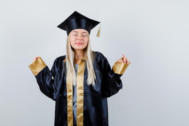 Fille blonde debout dans une pose de méditation en robe de graduation et casquette et l'air calme.