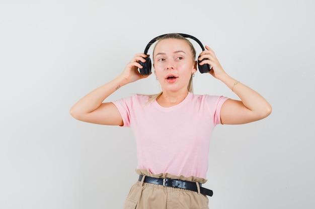 Fille Blonde Décoller Les écouteurs En T-shirt, Pantalon Et à La Vue étonnée, Avant. Photo gratuit