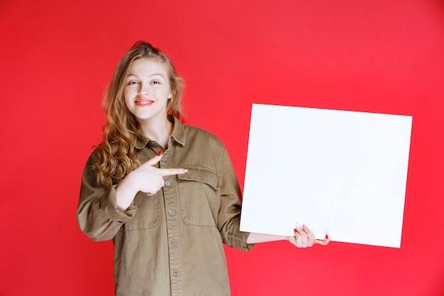 Fille blonde démontrant une œuvre d'art sur toile.
