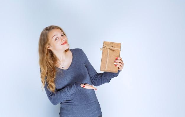 Fille blonde démontrant sa boîte-cadeau en carton et se sentant positive.