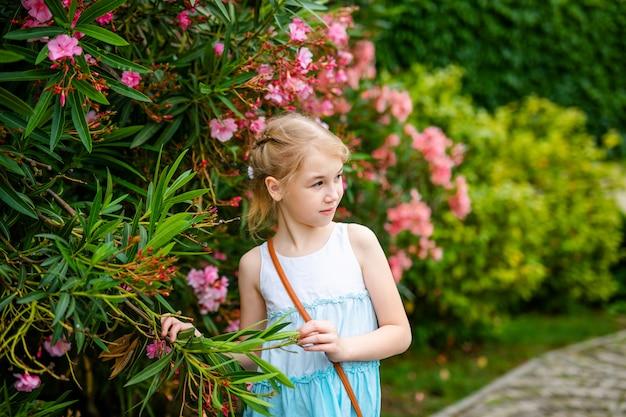 Fille blonde avec deux tresses en robe blanche et bleue restant parmi les arbres verts et les buissons à fleurs roses