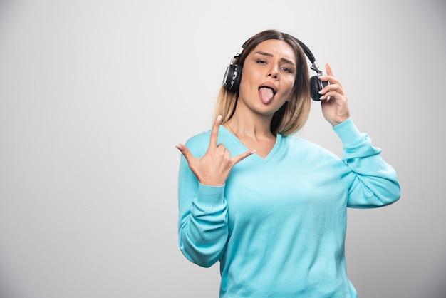 Fille blonde dj posant avec des écouteurs de manière positive.