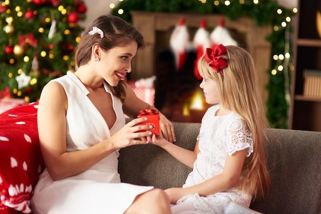 Fille blonde donnant un autre cadeau à maman