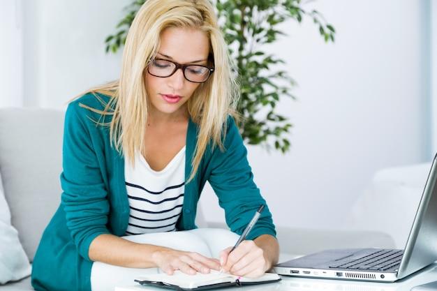 Fille blonde écrire quelque chose avec un ordinateur portable sur