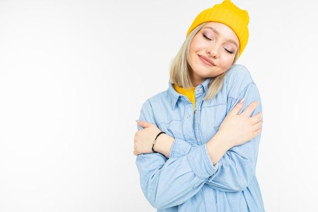 Fille blonde élégante au look décontracté se serre dans ses bras sur un fond blanc