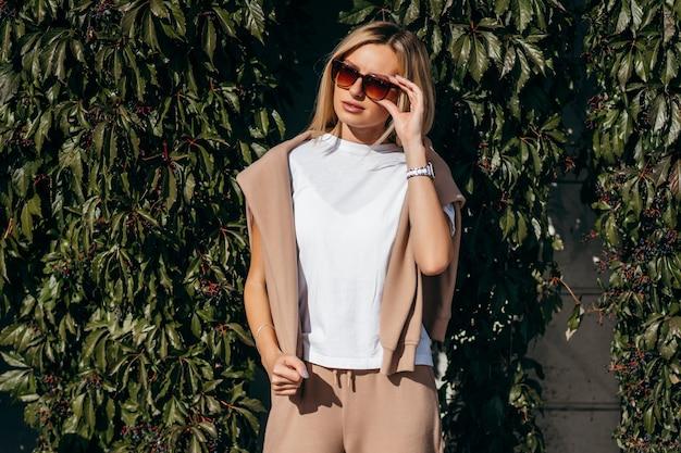 Fille blonde élégante portant des lunettes et t-shirt blanc