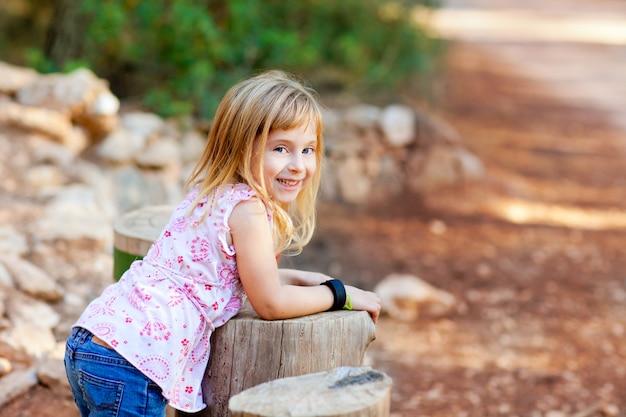 Fille blonde enfant dans la forêt de tronc