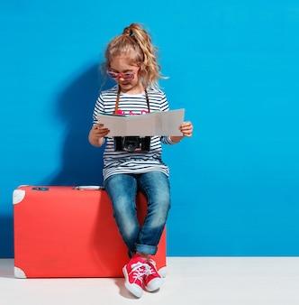 Fille blonde enfant avec valise vintage rose et plan de la ville prêt pour les vacances d'été. concept de voyage et d'aventure.