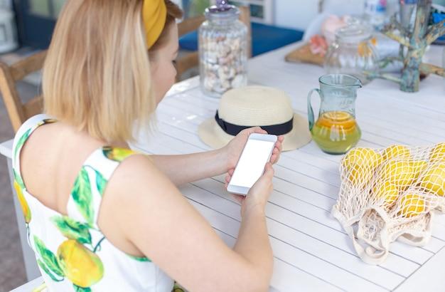 Une fille blonde est assise à une table blanche, tient un smartphone blanc dans ses mains, à côté se trouve une cruche de