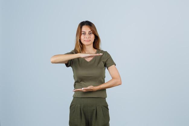 Fille blonde étirant la main comme tenant quelque chose dans un t-shirt et un pantalon vert olive et ayant l'air charmant. vue de face.