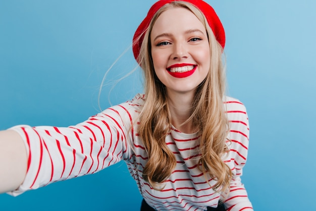 Fille blonde excitée en béret prenant selfie sur mur bleu. insouciante jeune femme en chemise rayée.