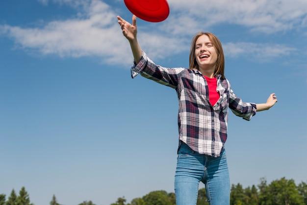 Fille blonde à faible angle jouant avec un frisbee rouge
