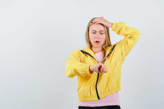 Fille blonde faisant semblant de regarder l'horloge en t-shirt rose et veste jaune et à la surprise
