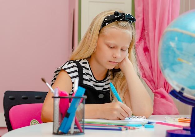 Fille blonde fait ses devoirs.