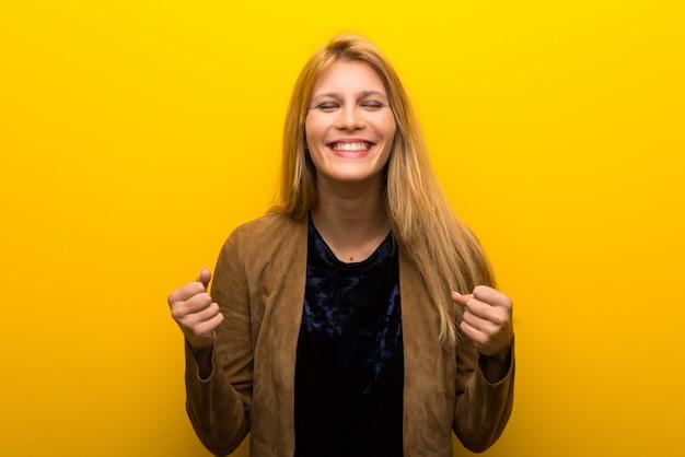 Fille blonde sur fond jaune vibrant célébrant une victoire en position de gagnant