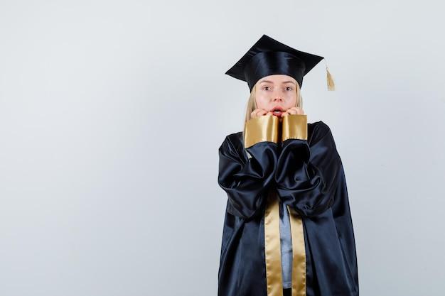Fille blonde gardant les mains près de la bouche en uniforme de diplômé et ayant l'air effrayé