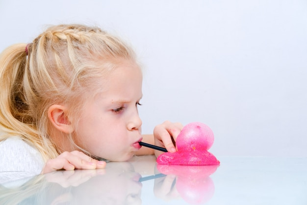Fille blonde gonfler la bulle de boue de paillettes roses