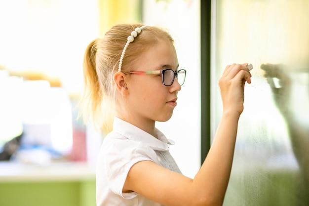 Fille blonde avec de grandes lunettes, assis dans la salle de classe, étudiant, souriant. education à l'école primaire, premier jour d'école