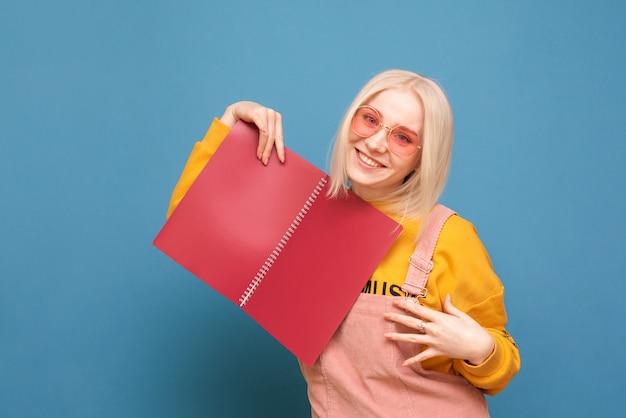 Fille blonde heureuse dans des vêtements lumineux et des lunettes roses pose avec un balai dans ses mains sur un bleu