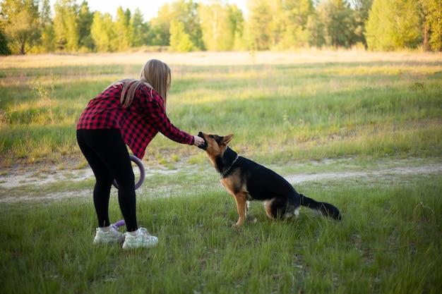Une fille blonde heureuse est jouée et élève un chien.