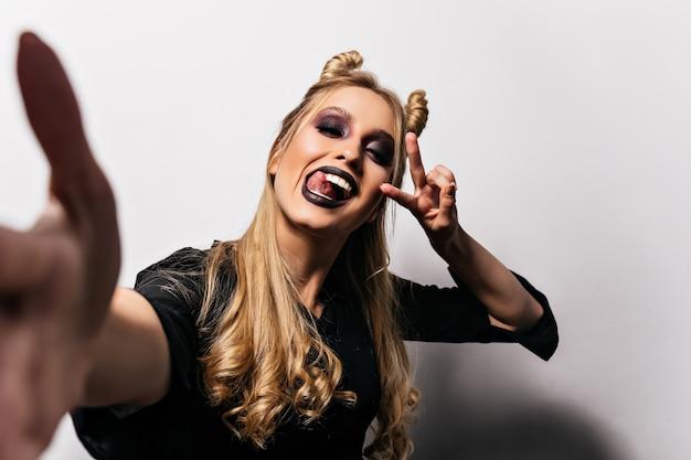 Fille blonde heureuse avec des lèvres noires faisant selfie à halloween. incroyable jeune sorcière drôle posant sur un mur blanc.