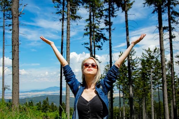 Fille blonde heureuse avec packpack dans une montagne.