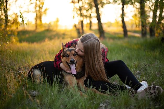 Une fille blonde heureuse se joue avec un chien.