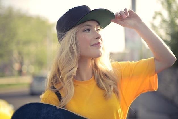 Fille blonde heureuse avec skateboard