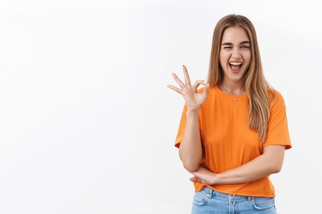 Une fille blonde impertinente montre un signe d'accord, un clin d'œil et un sourire, assure que vous aimerez cela, le meilleur choix jamais fait, garantit la meilleure qualité, satisfaite après avoir passé les cours, e-learning, confiante quant à la décision