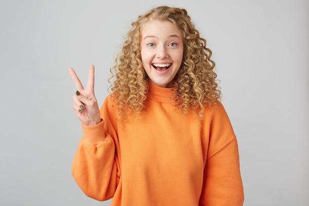 Fille blonde insouciante, joyeuse, aux cheveux bouclés aux yeux bleus sourit avec affabilité, montrant avec ses doigts un signe de paix