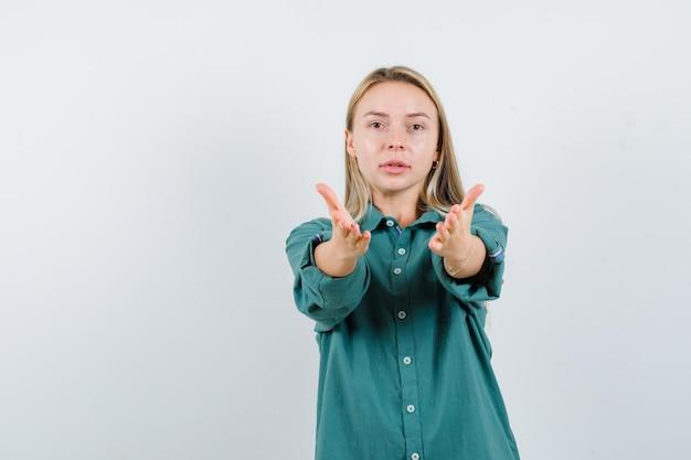 Fille blonde invitant à venir en blouse verte et semblant sérieuse