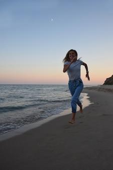 Une fille blonde en jeans et un t-shirt court le long du rivage de la mer du soir