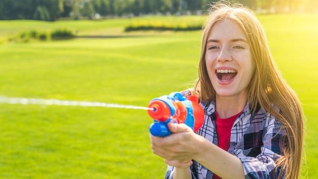 Fille blonde jouant avec un pistolet à eau