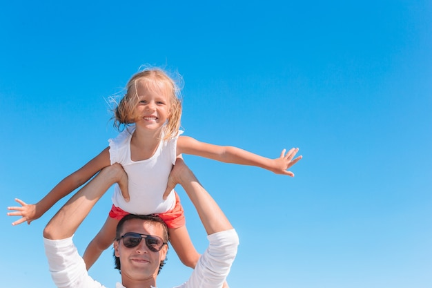 Fille blonde jouant avec son père à la plage