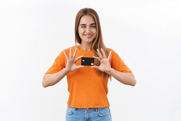 Une fille blonde joyeuse et impertinente recommande d'acheter en ligne, de faire des achats sur internet, de montrer une carte de crédit, de faire un clin d'œil et de sourire heureux, de donner des conseils où trouver des remises spéciales et les meilleures offres sur les produits