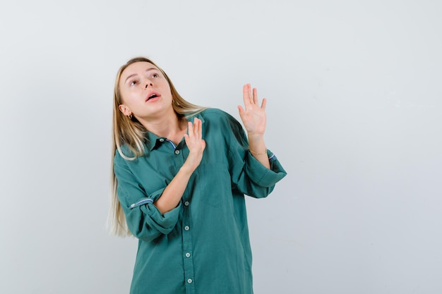 Fille blonde levant les mains dans la pose d'abandon en chemisier vert et l'air effrayé.