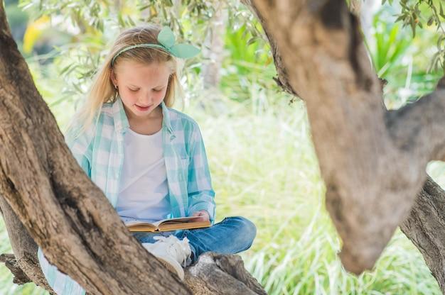 Fille blonde lisant un livre sur un grand arbre étalé.