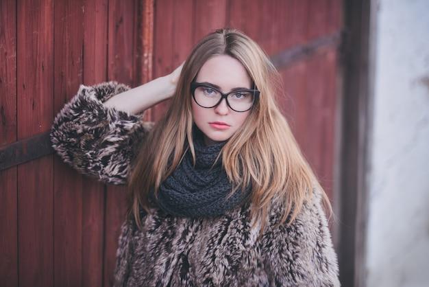 Fille blonde en lunettes de chat yeux dans un manteau de fausse fourrure artificielle posant.
