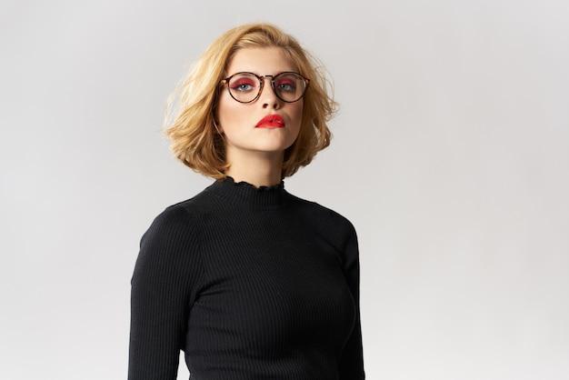 Fille blonde avec des lunettes chemisier noir lèvres rouges vue recadrée studio de lumière glamour.