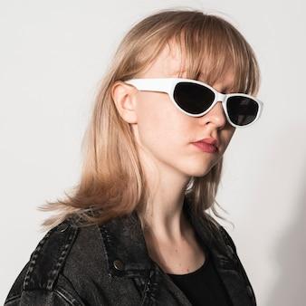 Fille blonde avec des lunettes de soleil blanches séance photo de mode pour adolescents