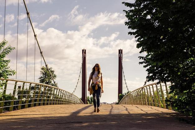 Fille blonde avec lunettes de soleil, casquette et veste dorée marchant sur le pont rouge au lever du soleil. berge de rivière. concept de style de vie et liberté.