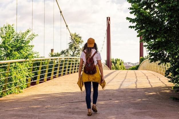 Fille blonde avec des lunettes de soleil, une casquette de veste dorée et un sac à dos en cuir marron marchant sur le pont rouge à l'aube. berge de rivière. concept de style de vie et liberté.