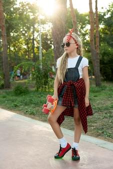 Fille blonde avec des lunettes de soleil et skateboard
