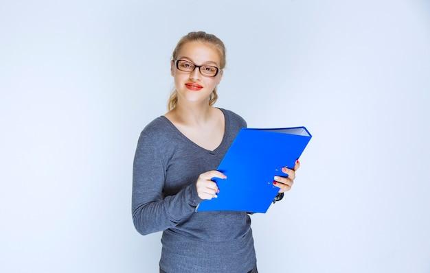 Fille blonde avec des lunettes tenant un dossier bleu et souriant.