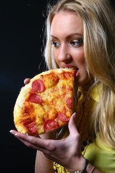Fille blonde mange de la pizza