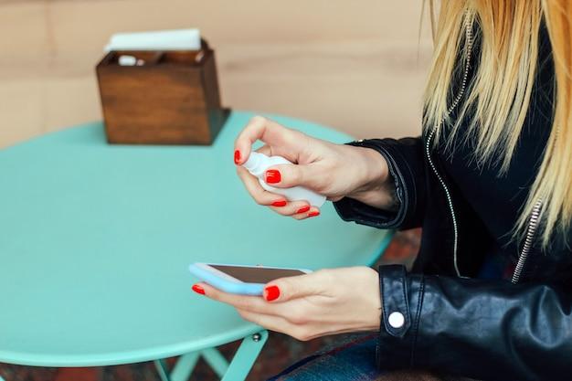 Une fille blonde avec une manucure rouge traite le téléphone avec un désinfectant contre les germes.
