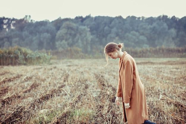 Une fille blonde marche seule sur le terrain vague. le concept de dépression